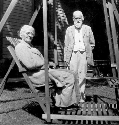 Mary seated in outdoor glider with C W standing nearby